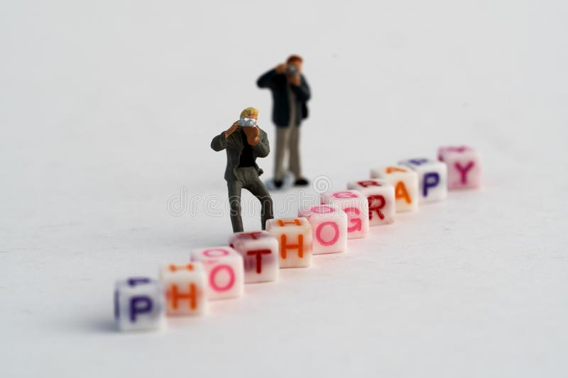 Miniature Photographers taking pictures behind a Group Of Letters forming Word Spelling stock photos