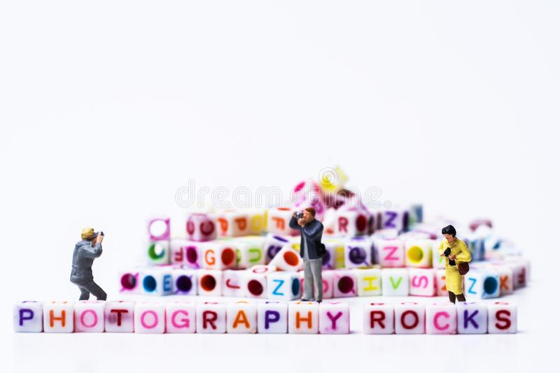 Miniature Photographers taking pictures before a Group Of Letters forming Words Spelling stock image