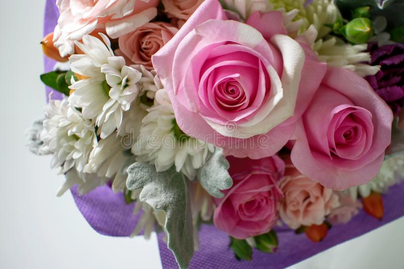Miniature pink roses and other flowers in this detail of a small royalty free stock photo