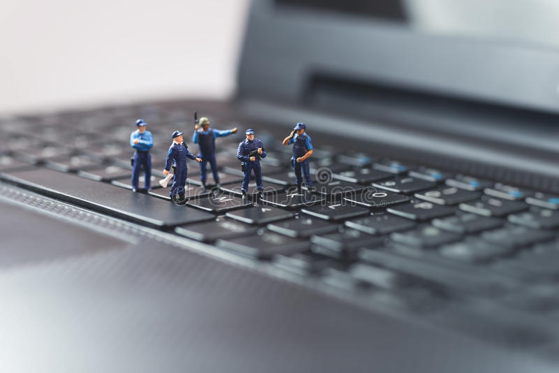 Miniature police squad protecting laptop computer. Technology concept.  royalty free stock image