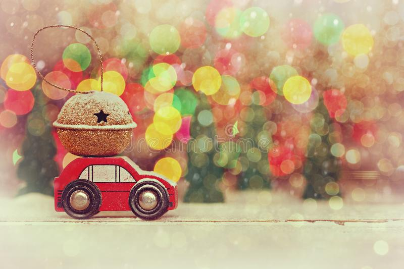 Miniature Red Car Carrying a Gift on roof on colorful bokeh background. Miniature Red Car Carrying a Gift on colorful bokeh background. Holiday Merry Christmas stock photo
