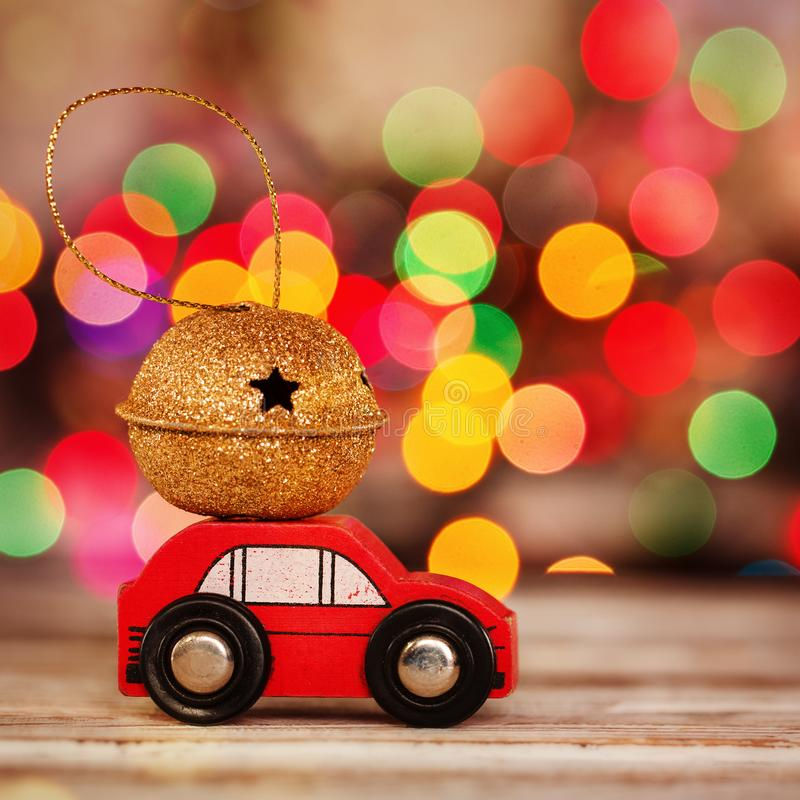 Miniature Red Car Carrying a Gift on roof on colorful bokeh background. Miniature Red Car Carrying a Gift on colorful bokeh background. Holiday Merry Christmas royalty free stock photography