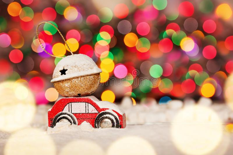 Miniature Red Car Carrying a Gift on roof on colorful bokeh background. Miniature Red Car Carrying a Gift on colorful bokeh background. Holiday Merry Christmas royalty free stock image