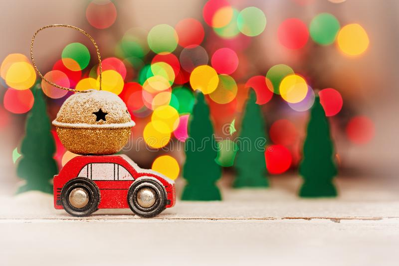 Miniature Red Car Carrying a Gift on roof on colorful bokeh background. Miniature Red Car Carrying a Gift on colorful bokeh background. Holiday Merry Christmas stock image