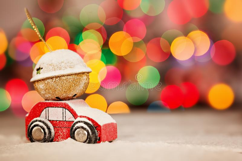 Miniature Red Car Carrying a Gift on roof on colorful bokeh background. Miniature Red Car Carrying a Gift in a snowy landscape. Holiday Merry Christmas concept stock images