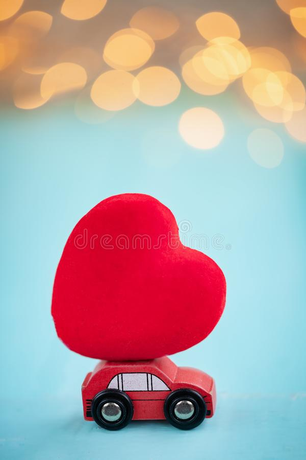 Miniature red car carrying a red heart on shine bokeh background. Miniature red car carrying red heart on shine bokeh background stock photos