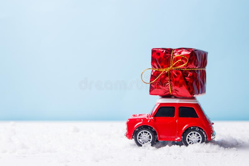 Miniature red car toy delivering gift box on blue background. Christmas greeting card concept royalty free stock image
