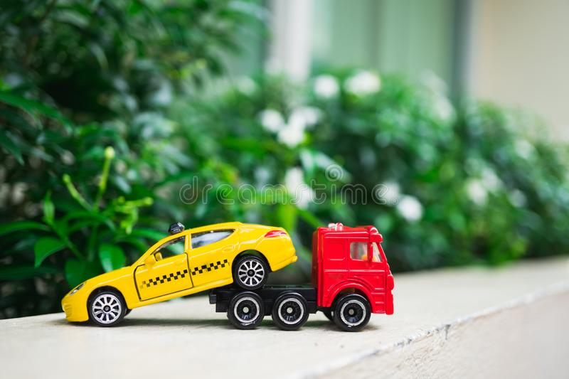 Miniature red trailer lift up broken yellow taxi using as transporation concept stock photo