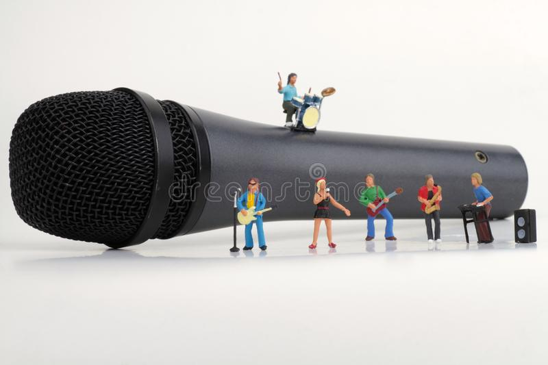 Miniature of a rock band. Performing on a microphone stock photo