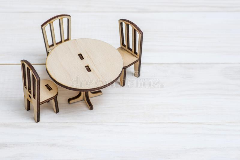 Miniature rustic wooden furniture on wooden background. Vintage table and chairs with copy space stock photos