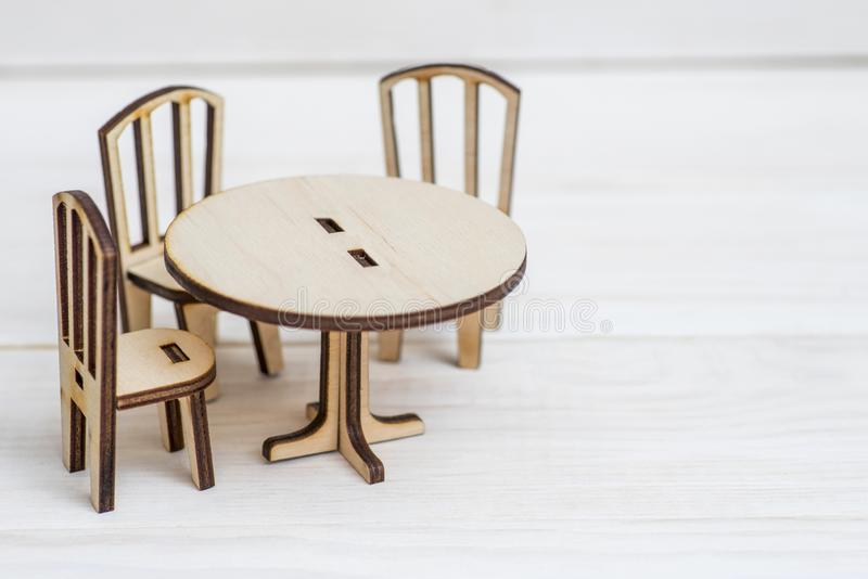 Miniature rustic wooden furniture on wooden background. Vintage table and chairs with copy space stock image