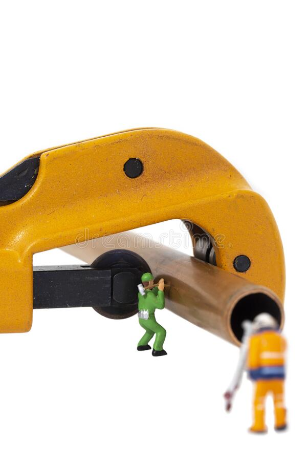 Miniature scale model construction workers with a copper pipe and a pipe cutter.  Plumbing industry concept royalty free stock photography