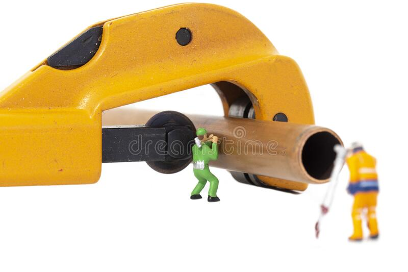 Miniature scale model construction workers with a copper pipe and a pipe cutter.  Plumbing industry concept stock photos