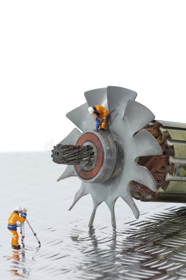 Miniature scale model construction workers with an industrial electric fan motor. royalty free stock photo