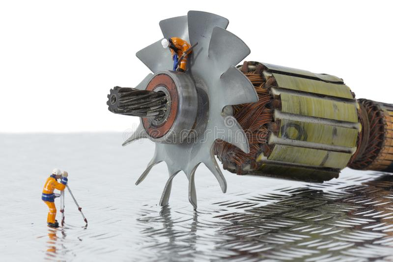 Miniature scale model construction workers with an industrial electric fan motor. stock photo