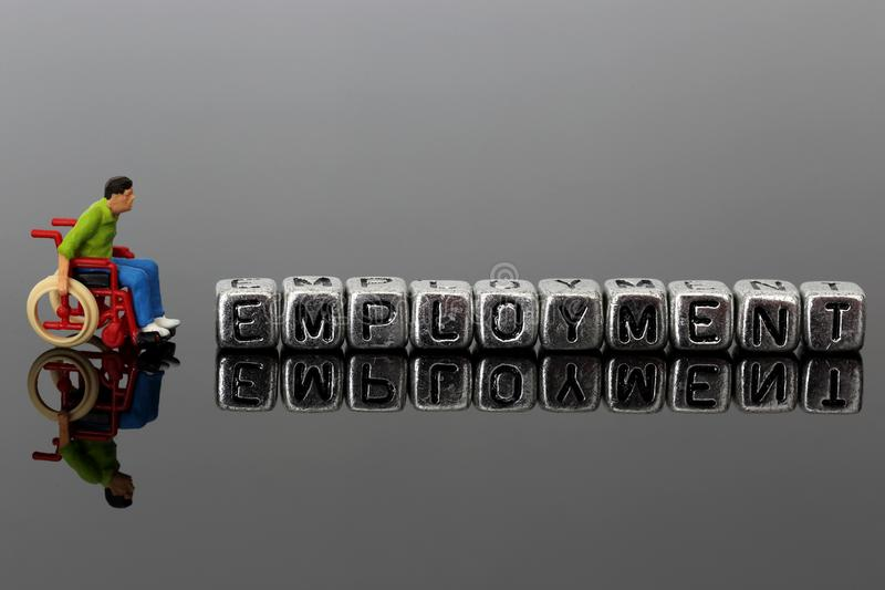 Miniature scale model man in a wheelchair with the word employment on beads stock image