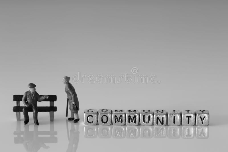 Miniature scale model senior pensioners talking with the word community. On beads stock photos