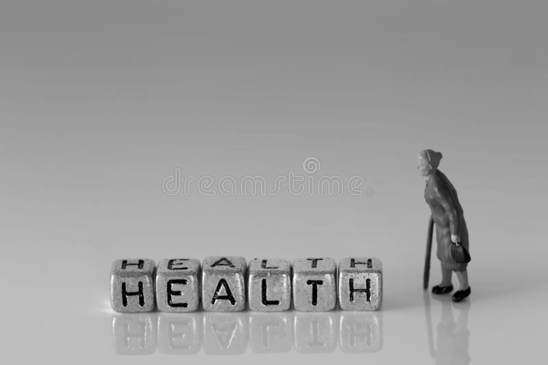 Miniature scale model senior pensioners talking with the word health royalty free stock photo