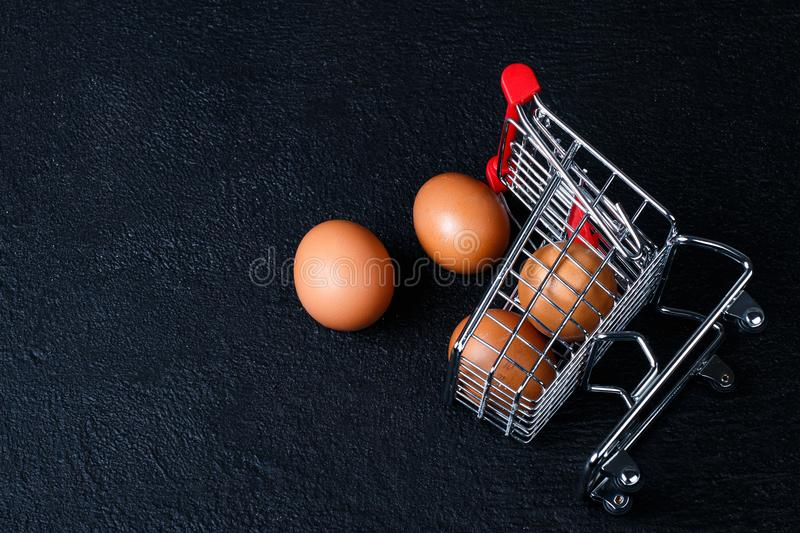 Miniature shopping cart with eggs. Shopping cart full of eggs, isolated on black background royalty free stock image