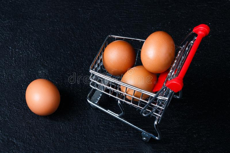 Miniature shopping cart with eggs. Shopping cart full of eggs, isolated on black background stock photography