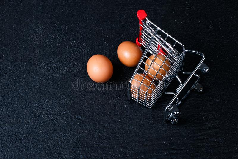 Miniature shopping cart with eggs. Shopping cart full of eggs, isolated on black background stock image