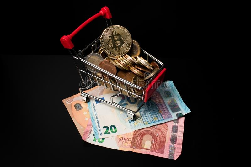 Miniature shopping cart filled with Euro coins and a bitcoin on the top placed on paper money with a black background. royalty free stock photo