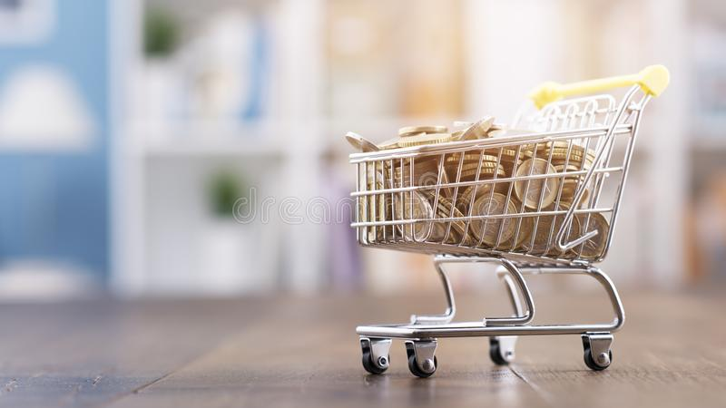 Miniature shopping cart full of coins stock photography