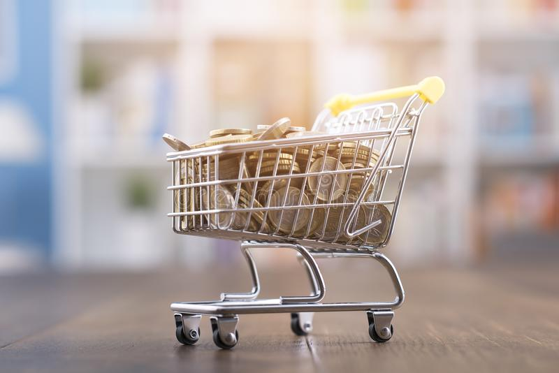 Miniature shopping cart full of coins royalty free stock images
