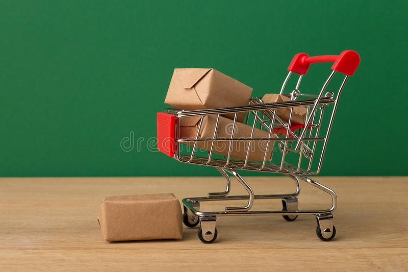 Miniature shopping cart and parcels on brown background, royalty free stock photos