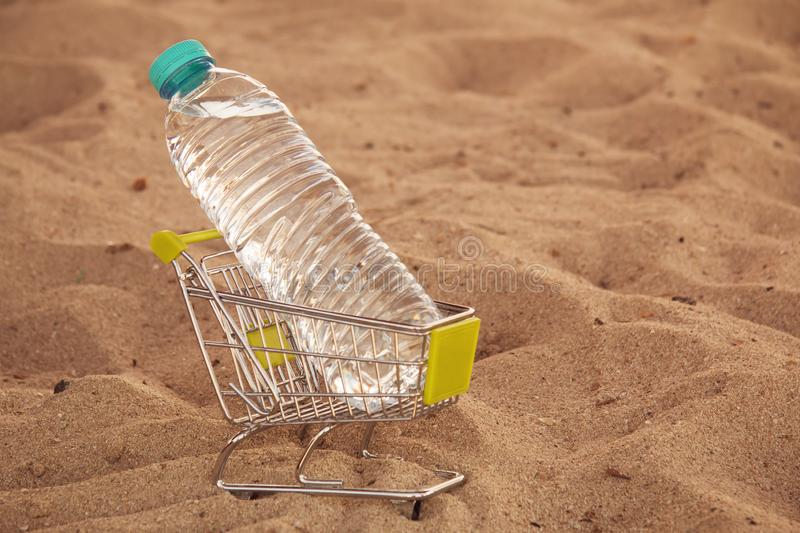 Miniature shopping cart with plastic bottle with water left by tourist on a tropical beach. Water is a sellable royalty free stock images
