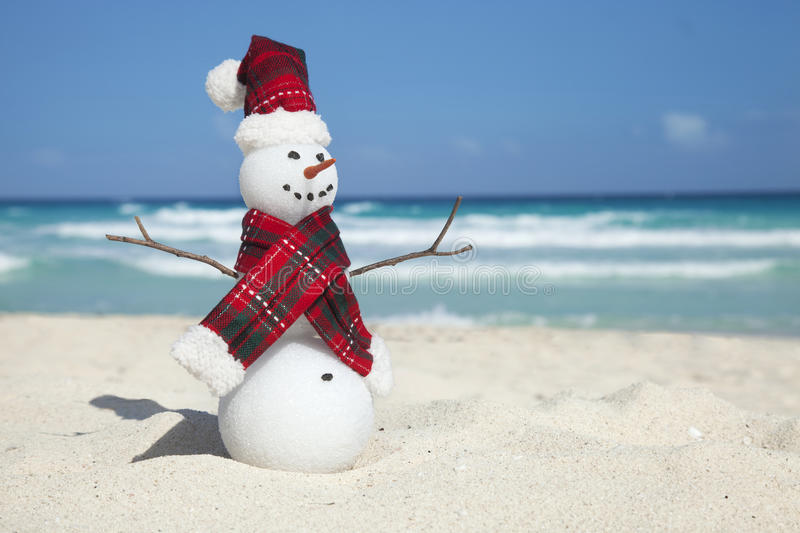 Miniature Snowman Wearing Hat and Scarf on the Beach stock image