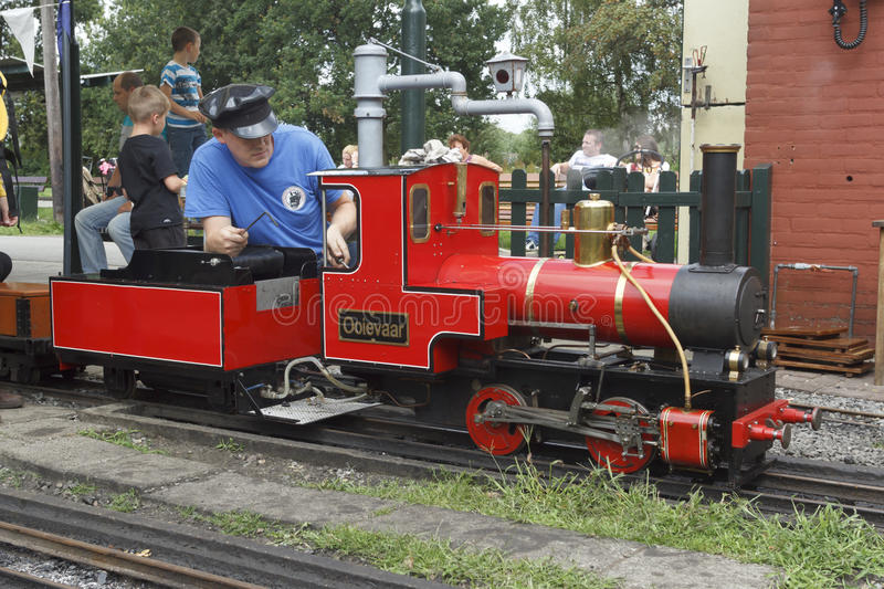 Miniature Steam Train. Steam miniature train driver preparing the locomotive for an imminent departure stock images