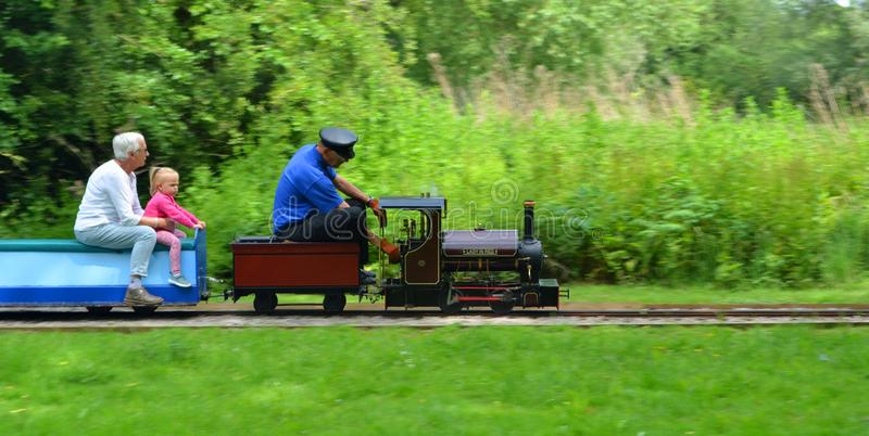 Miniature Steam train giving adults and children rides in the park. royalty free stock photos