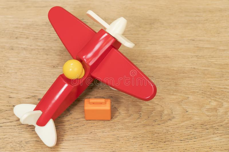 Miniature suitcase and toy plane on table stock photos