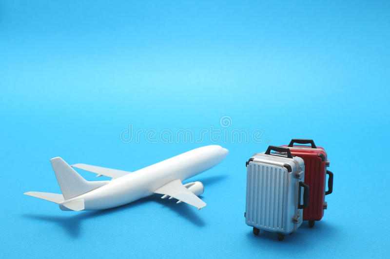 Miniature toy airplane and suitcase on blue background. royalty free stock images