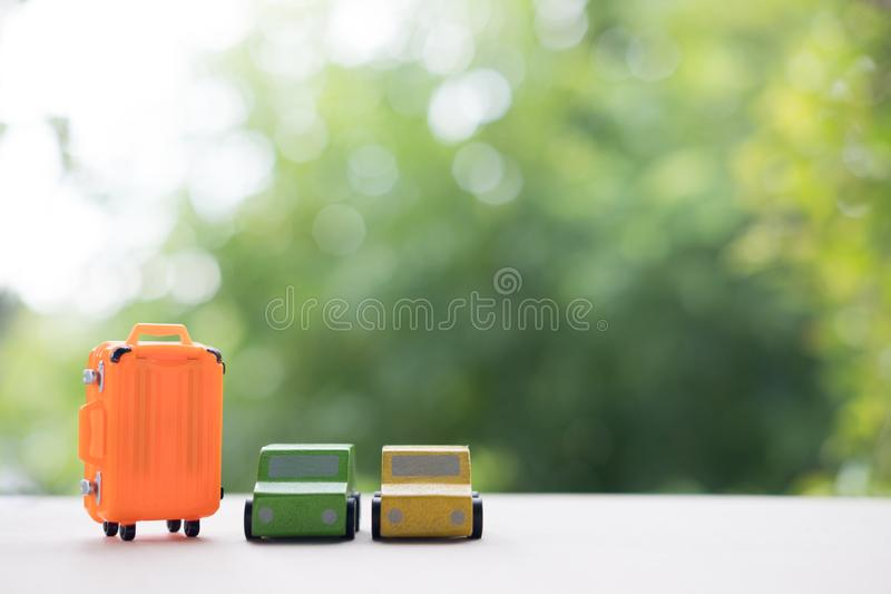 Miniature toy car and miniature orange suitcases on nature background royalty free stock images