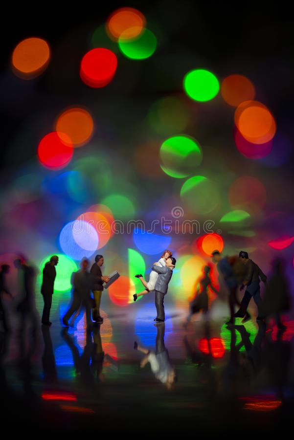 Miniature toy -A couple hugging together among busy commuters crowd with colorful bokeh lights, happiness concept.  stock images