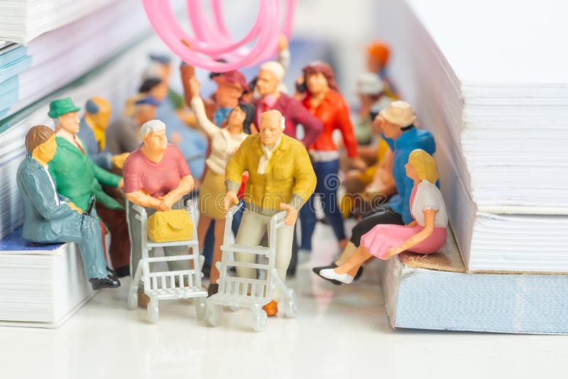 Miniature toy of couple of senior citizen on a public transport concept royalty free stock photo