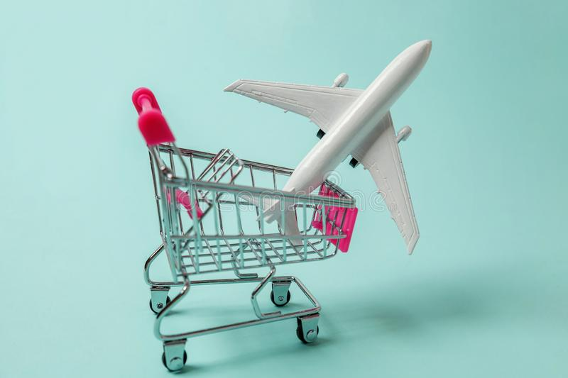 Toy plane and shopping push cart on blue background stock photos