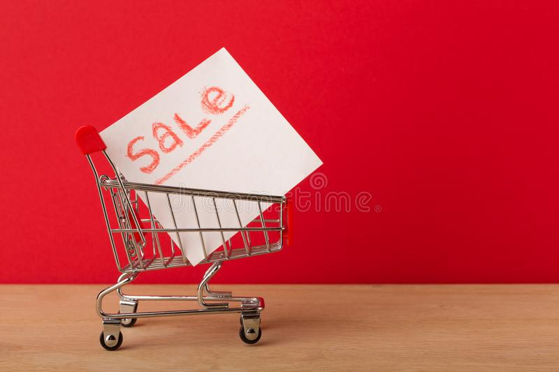 Miniature shopping cart and label with sale royalty free stock photography