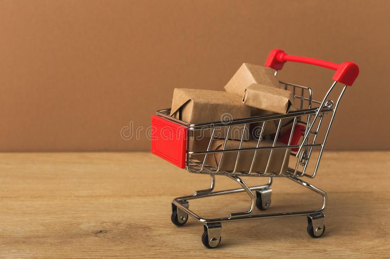 Miniature shopping cart and parcels on brown background, royalty free stock images
