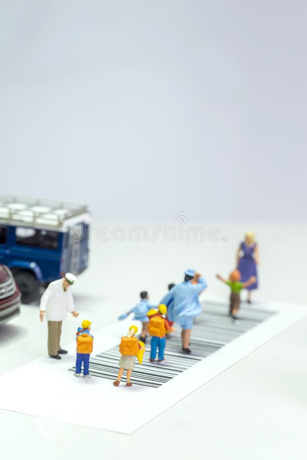 Miniature toys school kids walk on cross road bar code - school children road safety concept - top view royalty free stock photography
