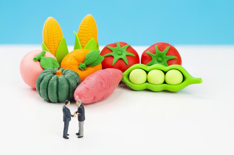 Miniature toys studio set up - two businessman shakes hand in agreement concept with fresh produce in the background stock photo
