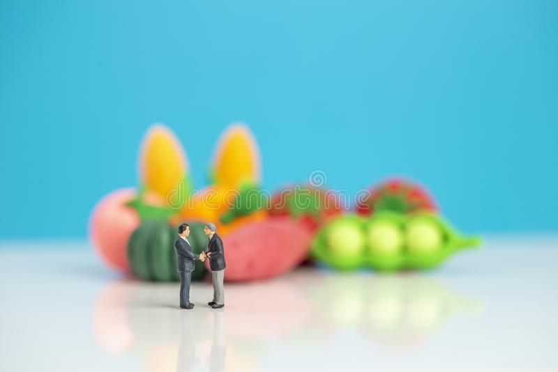 Miniature toys studio set up - two businessman shakes hand in agreement concept with fresh produce in the background stock image