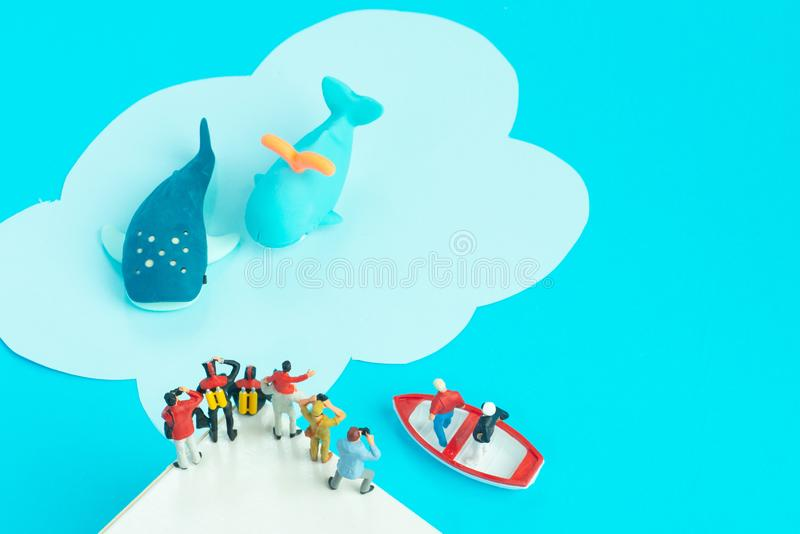 Miniature toys - whale watching expedition-father and son, scuba divers, photographers and man with binocular stock photo