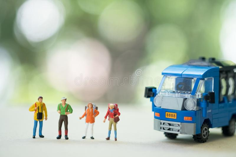 Miniature traveler with backpack hitchhiking on the rural road at Thailand in summer. Miniature people : Traveler with backpack hitchhiking on the rural road at stock photography