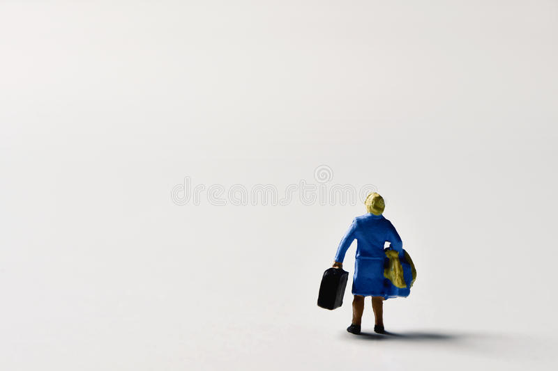 Miniature traveler woman with suitcases. Miniature traveler woman seen from behind carrying some suitcases on an off-white background with a large blank space on stock image