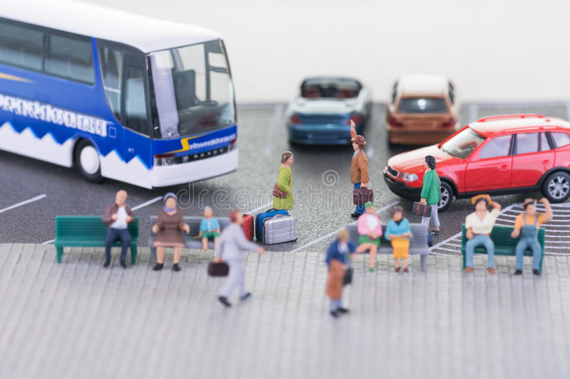 Miniature travellers with coach and cars close-up. Miniature travellers at a bus station royalty free stock image