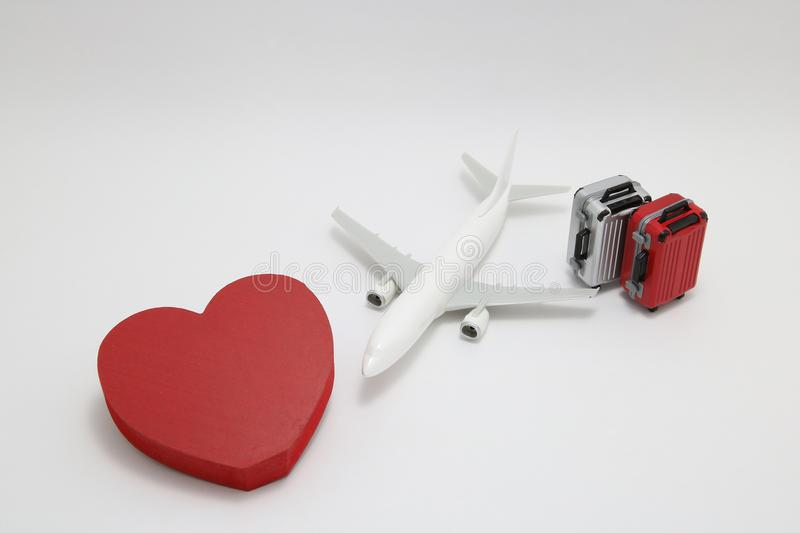Miniature two suitcases, miniature toy airplane, and a red heart on white background. royalty free stock photo