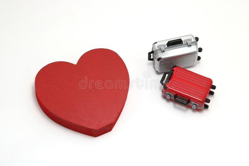 Miniature two suitcases and a red heart on white background. royalty free stock photography
